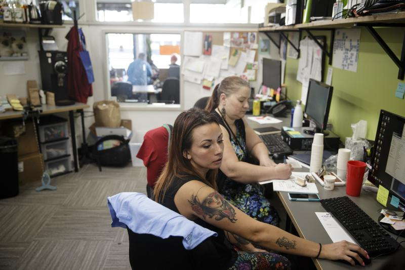 Amber Lakin (front) and colleague Julia Porras work at Central City Concern, an organization that does outreach and job training to combat homelessness and addiction in Portland, Ore. Lakin went through the welfare system and now works with Central City C