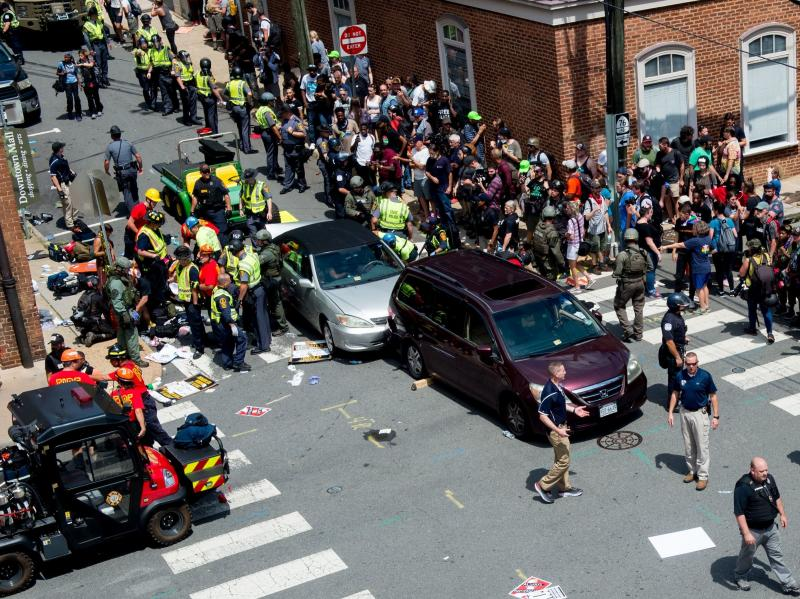 People receive first aid after a car ran into a crowd of protesters in Charlottesville, Va., on Saturday. The car struck the silver vehicle pictured, sending marchers into the air.