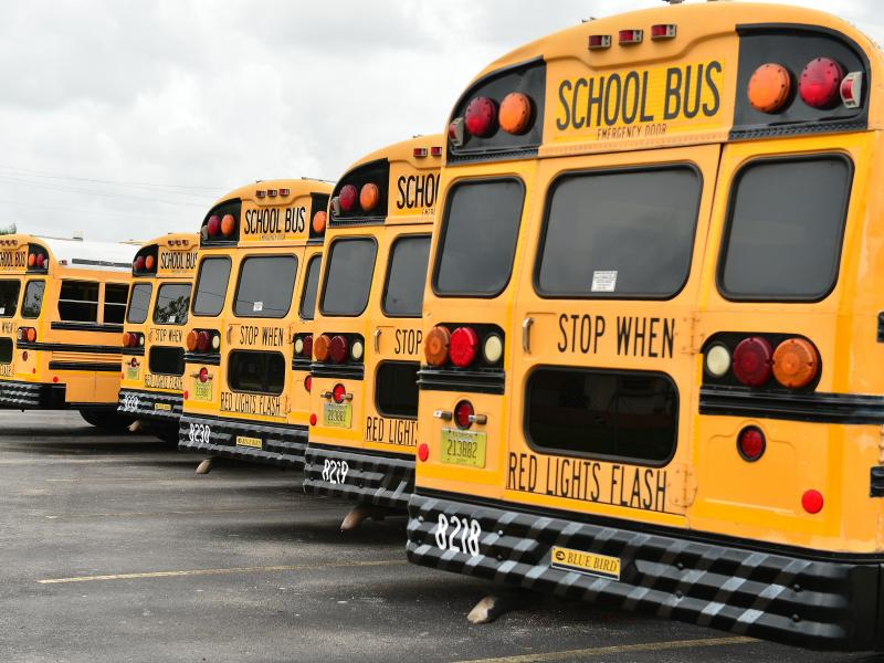A fleet of Broward County School Buses are parked in a lot on July 21, 2020, in Pembroke Pines, Fla. Three county educators have died of complications from the coronavirus.