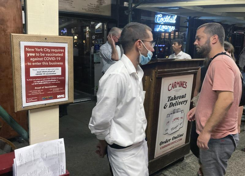 A sign in August informs customers that they must show proof of vaccination against COVID-19 in order to dine indoors at Carmine's Italian restaurant in Manhattan.