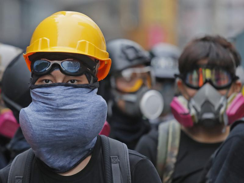Protesters with protective gear face riot police on a Hong Kong street during the anti-extradition bill protests in August. Beijing is moving to pass a law that could outlaw such protests.