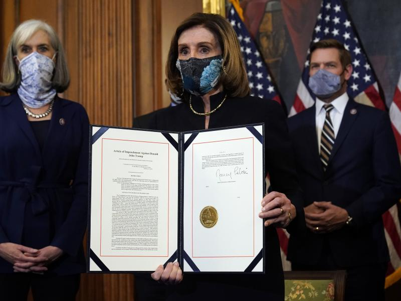 House Speaker Nancy Pelosi of California displays the signed article of impeachment against President Trump in an engrossment ceremony before transmission to the Senate for trial on Capitol Hill. It's unclear when a Senate trial will start.