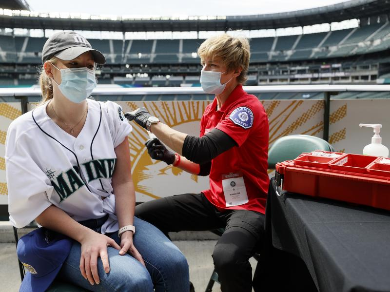 Sydney Porter of Bellevue, Wash., receives her COVID-19 vaccination from Kristine Gill, with the Seattle Fire Department's Mobile Vaccination Teams, before the game between the Seattle Mariners and the Baltimore Orioles at T-Mobile Park on May 5 in Seattl