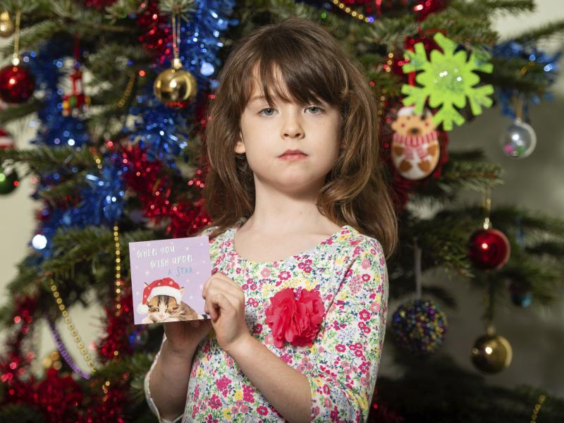 Florence Widdicombe, 6, poses with a Christmas card from the same pack as a card she found containing a message apparently from foreign prisoners in China. The U.K.-based grocery chain Tesco has halted production at the factory in China that supplied the