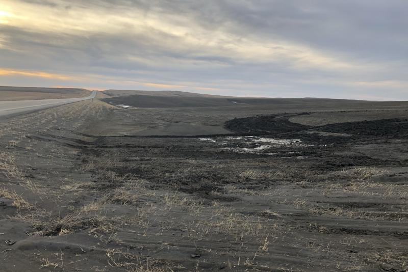 Wind-blown soil fills a ditch between a road and the fields of Gunsmoke Farms, a large organic farm northwest of Pierre, S.D., in early March.