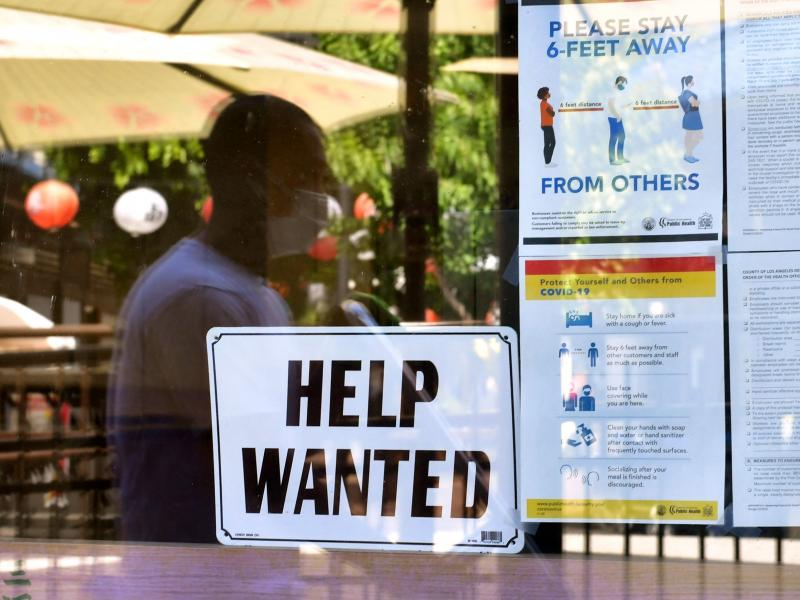 """A """"Help Wanted"""" sign is posted beside coronavirus health safety guidelines at a restaurant in Los Angeles on May 28. Businesses are desperate for workers even as millions remain unemployed. Republican governors blame a major unemployment benefit passed du"""