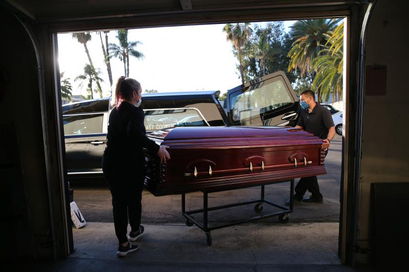Embalmer and funeral director Kristy Oliver (left) and funeral attendant Sam Deras load the casket of a person who died after contracting COVID-19 into a hearse in El Cajon, Calif. People who work in hospitals and in funeral homes are witnesses to the los