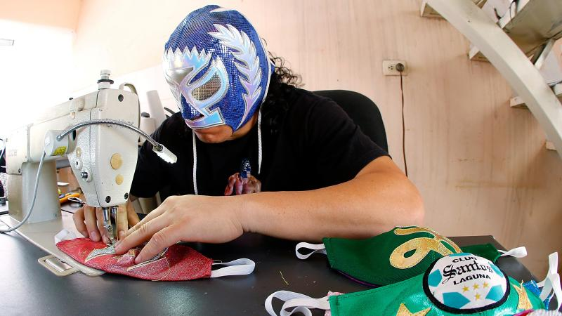 Mexican lucha libre wrestler Hijo del Soberano sews face masks since his matches have stopped due to the COVID-19 pandemic.