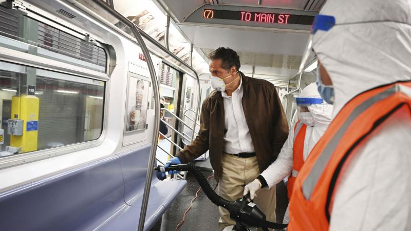 Gov. Andrew Cuomo tries out a spraying device on a New York City subway car during a visit to the Metropolitan Transportation Authority on Saturday.