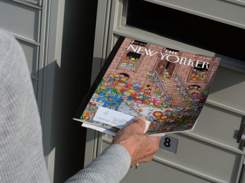 A woman retrieves a copy of The New Yorker magazine from her mailbox in Santa Fe, N.M., in 2020.