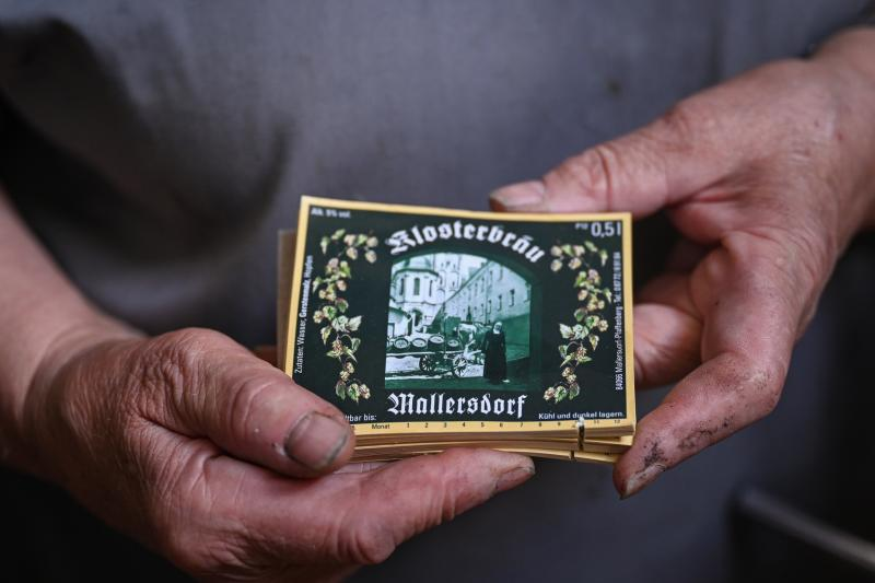 Sister Doris holds labels of the beer bottles with a painting of the former nun who was running the brewery.