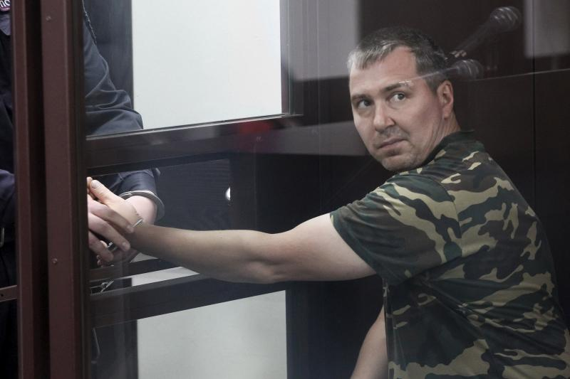Alexander Popov, who was arrested on suspicion of murder in the death of Catherine Serou, sits behind the glass in a courtroom in the Russian city of Gorodets on June 20.