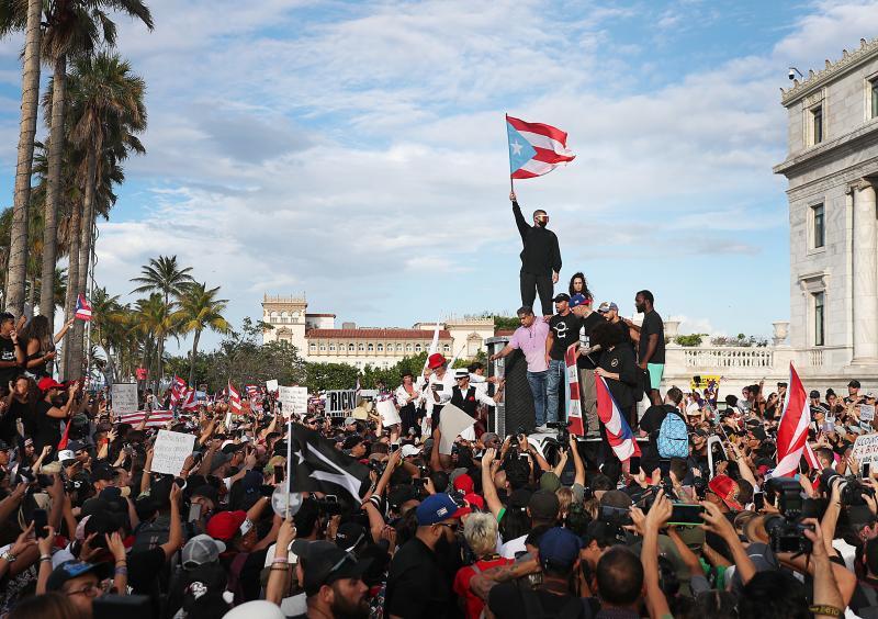 Bad Bunny (holding flag), singer Ricky Martin (in black hat) and Residente (in blue hat) join demonstrators in protest against Puerto Rico Gov. Ricardo Rosselló in Old San Juan.