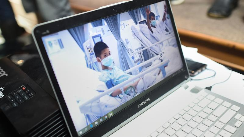 Local government workers on Wednesday display the newly released video footage of the rescued soccer players, who are currently recuperating in hospital beds.