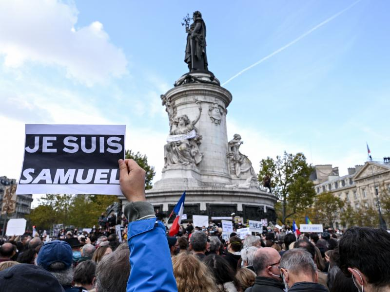 """Demonstrators like the one shown here carried """"I am Samuel"""" signs as they gathered on Place de la République in Paris on Sunday to pay tribute to slain history teacher Samuel Paty. Similar gatherings took place in several other cities as France reels fro"""