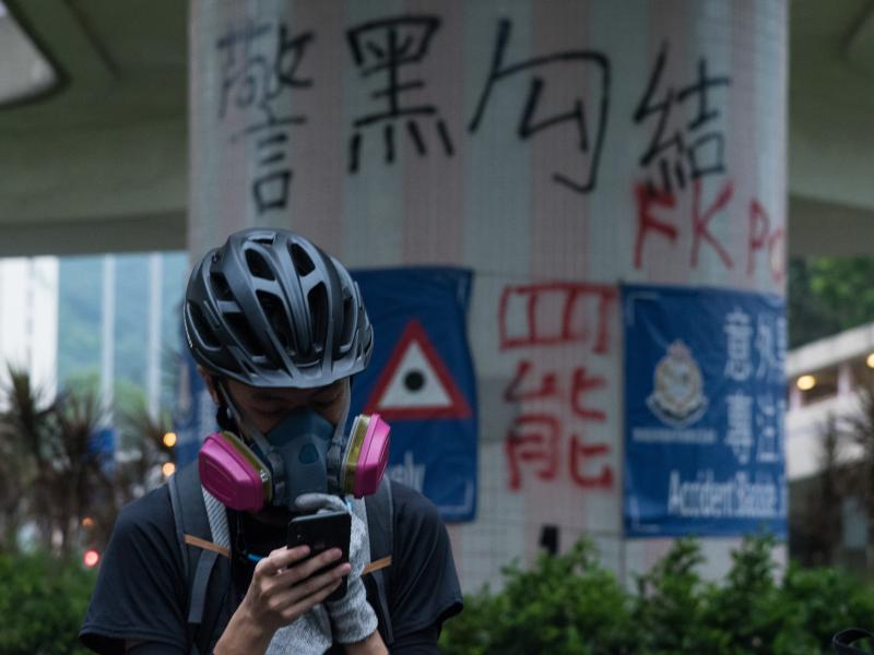 A protester in Hong Kong checks his phone for police activity during a protest against the government in Hong Kong's New Territories, in August.