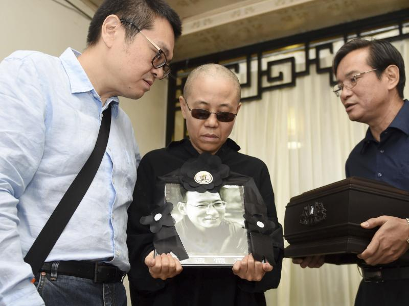 In a photo provided Saturday by the Shenyang Municipal Information Office, Liu Xia, center, the widow of Chinese dissident Liu Xiaobo, holds a portrait of him during his funeral. She stands with Liu Hui, her younger brother (left) and Liu Xiaoxuan, the yo