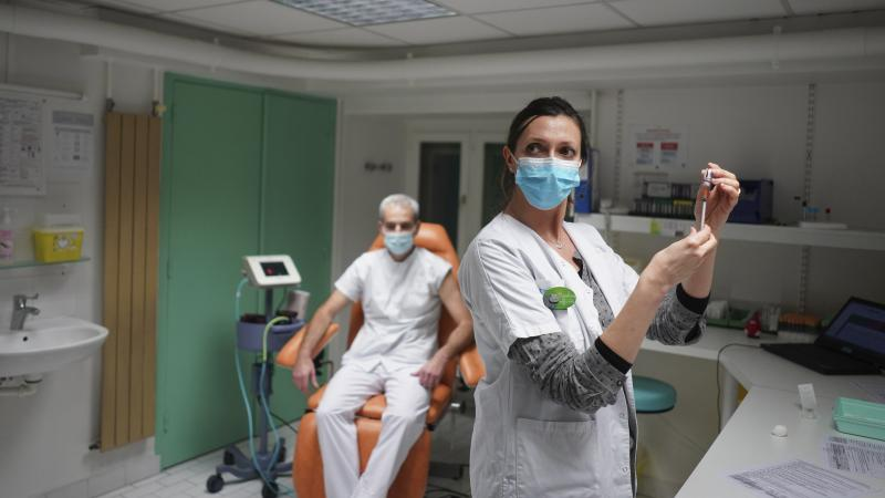 """A nurse prepares to administer the Pfizer-BioNTech COVID-19 vaccine to Dr. Jean-Christophe Richard in La Croix-Rousse hospital, in Lyon, France, on Wednesday. Amid public outcry, France's health minister promised Tuesday an """"exponential"""" acceleration of h"""