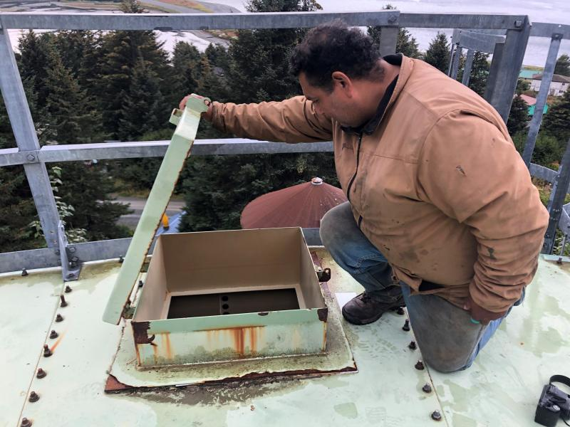 """Resident Anthony Brewster checks to see how much water is in Nanwalek's storage tank. The village has been on a """"boil water"""" notice for weeks."""