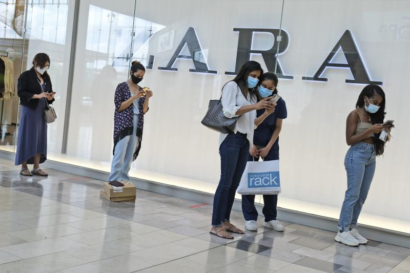 Customers wait in line to enter a Zara store inside the newly reopened Garden State Plaza mall in Paramus, N.J., on June 29.