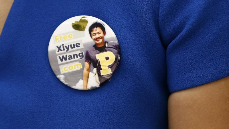 Hua Qu, the wife of Xiyue Wang, a Princeton University graduate student being held at an Iranian prison, wears a button bearing a picture of her husband as she speaks at a news conference to mark the third anniversary of his imprisonment, Aug. 8, 2019, in