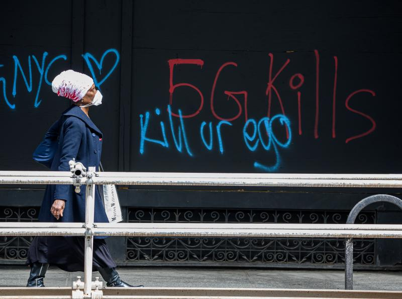 A pedestrian walks past anti-5G graffiti in the Flatiron District of New York in May.