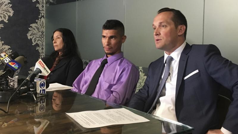 Jose Luis Conde (center) listens to news media while seated between his mother, Rosa Conde, and his attorney Bret Royle at Royle's office in Phoenix on Thursday. Royle released Mesa police body cam videos showing officers punching Conde, who was unarmed,