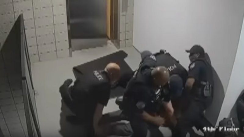 A still from surveillance footage, released by the police department in Mesa, Ariz., shows officers surrounding a man after they punched him to the ground.