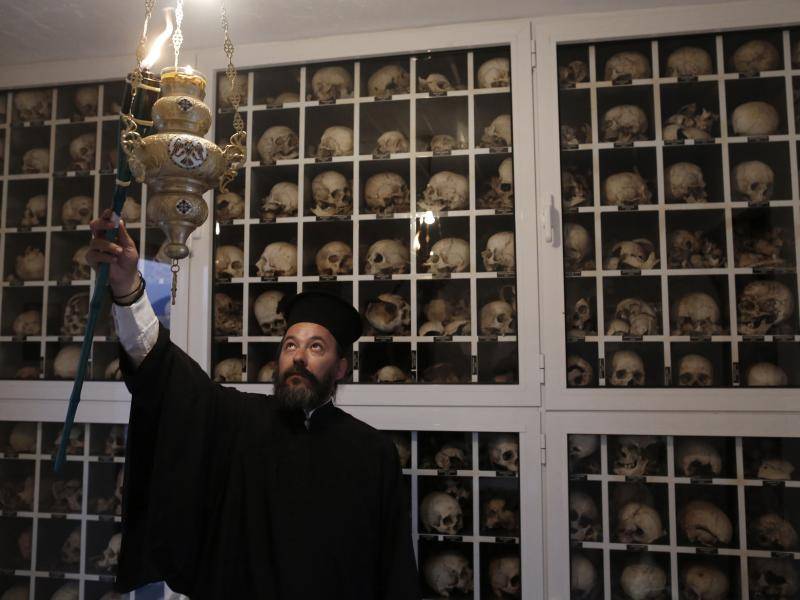 Greek Orthodox priest Apostolos Stavropoulos, 41, lights a torch inside the mausoleum in the village of Distomo in June 2013 on the eve of the 69th anniversary of the massacre committed by the Nazis during World War II. The remains of the more than 200 vi