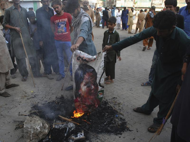 Pakistani protesters earlier this month burn a poster depicting Asia Bibi, who spent eight years on death row on blasphemy charges before being acquitted by Pakistan's Supreme Court.