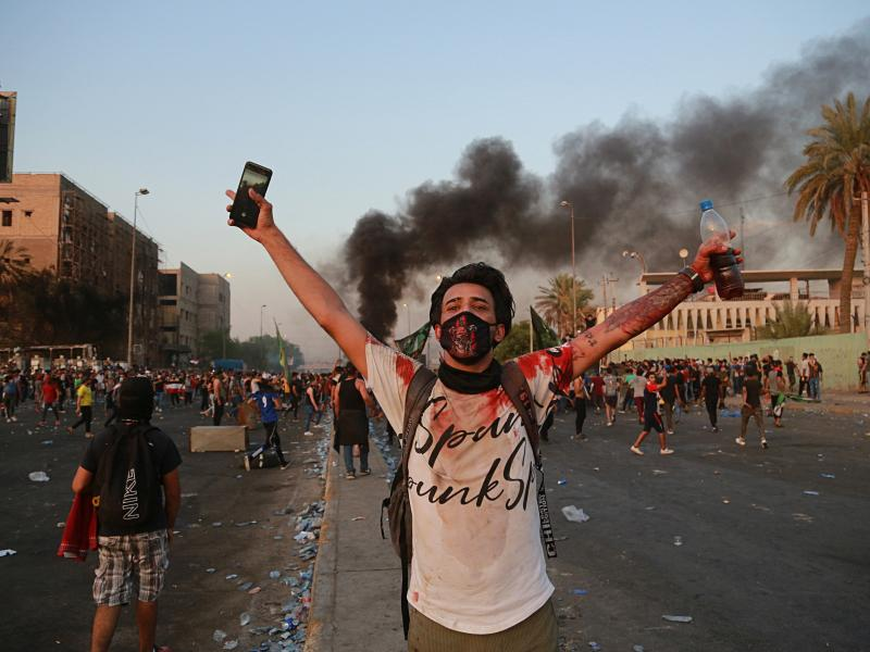 Anti-government protesters set fires and close a street during a demonstration in Baghdad on Thursday.