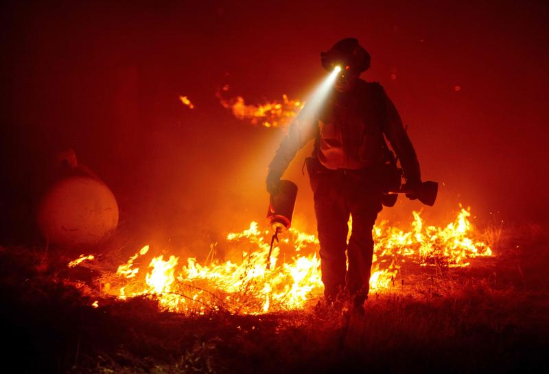 Firefighters cut defensive lines and light backfires to protect structures behind a Cal Fire fire station at the Bear Fire, part of the North Lightning Complex of fires in the Berry Creek area of Butte County, Calif., on Wednesday.