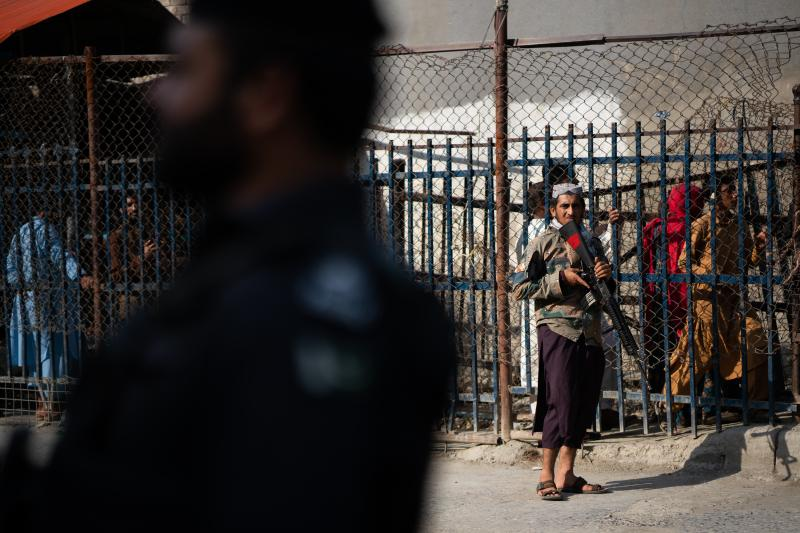 A Taliban guard stands on the Afghan side of the Torkham border crossing with Pakistan. People behind wait either to leave Afghanistan or to receive those returning to the country.