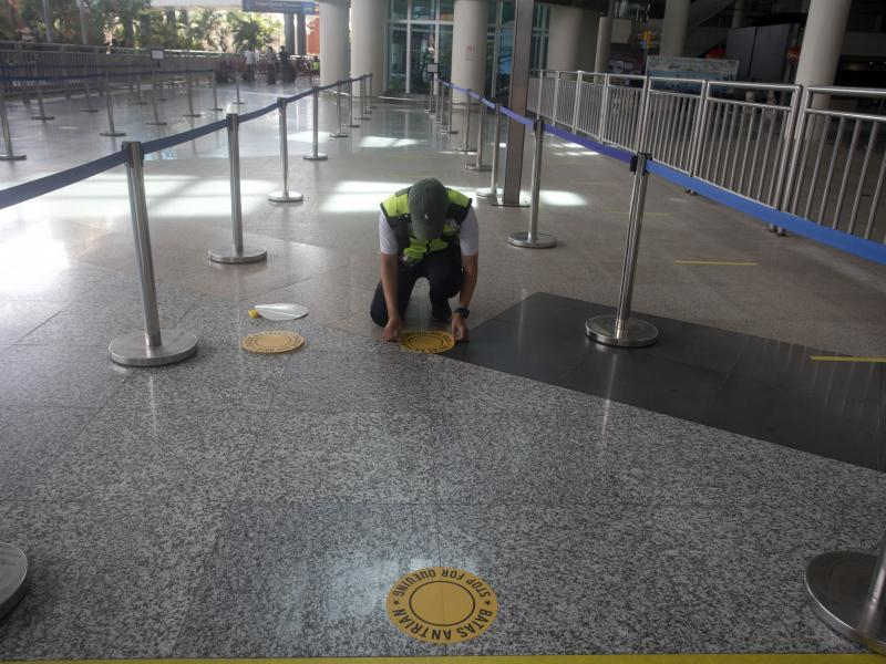 An airport worker marks queue line for the reopening of International Ngurah Rai Airport in Bali, Indonesia, Thursday.