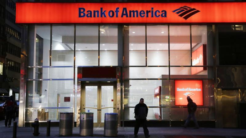 People walk past a branch of Bank of America in New York City in 2015. The bank announced Tuesday that it's raising its minimum wage to $20 an hour by 2021.