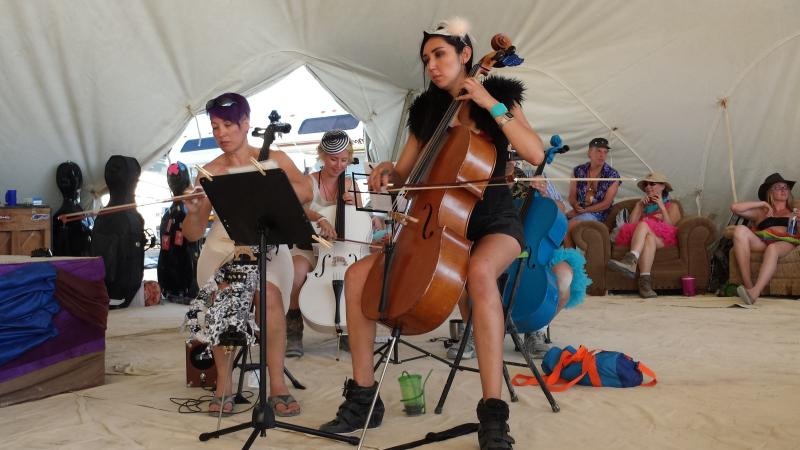 Cellists with the Playa Pops Symphony warm up before performing at Burning Man in 2014.