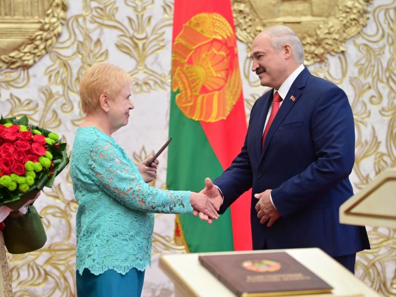 Lidia Yermoshina (left), chairperson of the Belarusian Central Election Commission, hands over a presidential ID to President Alexander Lukashenko during an inauguration ceremony Wednesday at Independence Palace in Minsk.