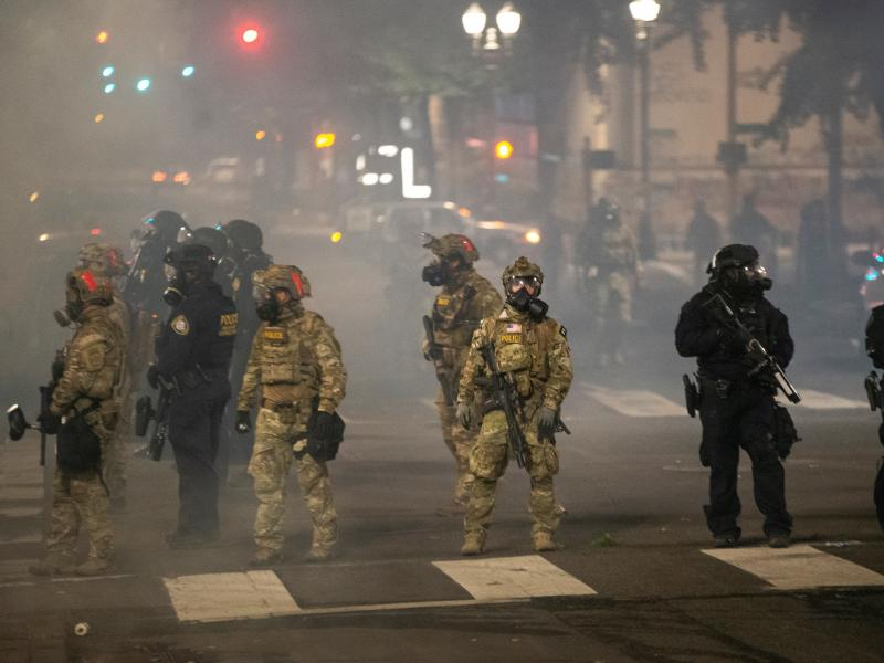 Federal police stand guard on Salmon Street after pushing protesters away from the Mark O. Hatfield U.S. Courthouse on Tuesday in Portland, Ore. The federal police response to the ongoing protests against racial inequality has been criticized by city and