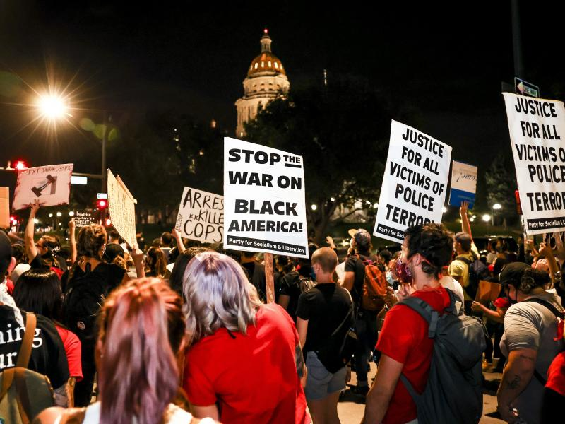 People protest the grand jury decision in the Breonna Taylor case in front of the Colorado state Capitol in Denver on Wednesday. As the protest was breaking up, a motorist drove through a small crowd of protesters who had yelled at the driver to turn arou