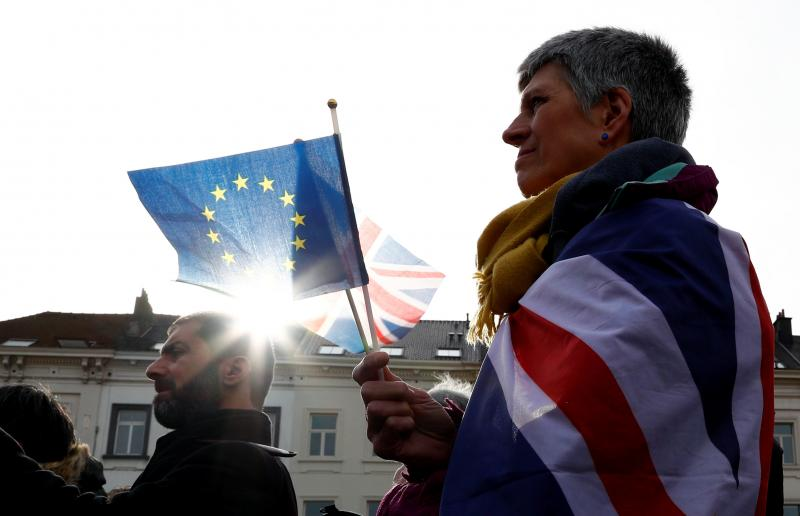 An anti-Brexit demonstrator holds British and European Union flags during a protest in front of the European Parliament in Brussels on Thursday.