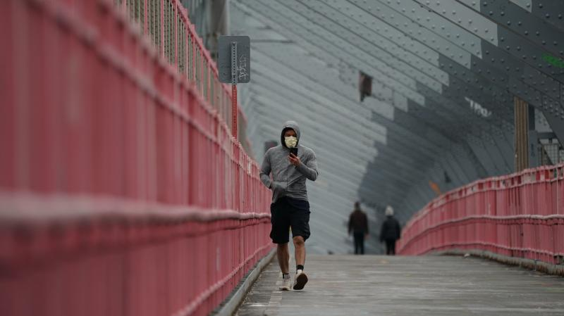 A pedestrian in a face mask crosses the Williamsburg Bridge in New York City last month. U.S. health authorities have announced they're changing the official recommendations on face masks, now urging people to wear them in public spaces to help slow the s