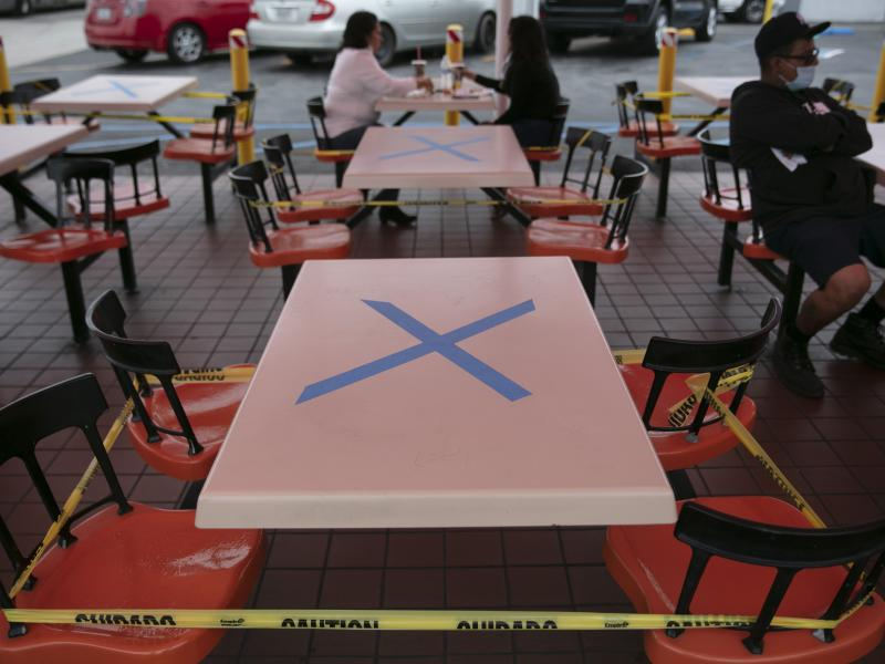 Tables are marked with X's for social distancing in the outdoor dining area of a restaurant in Los Angeles, Wednesday. California Gov. Gavin Newsom has ordered a three-week closure of bars and indoor operations of restaurants and certain other businesses