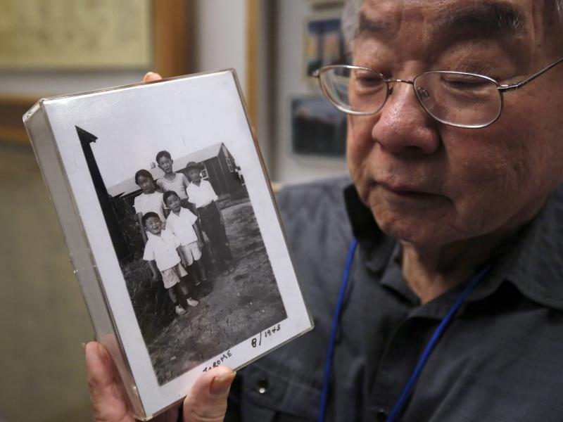During a visit last week to the California Museum in Sacramento, Les Ouchida holds a 1943 photo of himself (front row center) and his siblings taken at the internment camp in Jerome, Ark., that his family was moved to from their home near Sacramento in 19