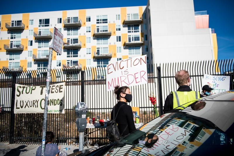A demonstrator holds a sign in the Mission in San Francisco on Nov, 16 calling for shelter-in-place hotel rooms to remain available for unhoused residents.