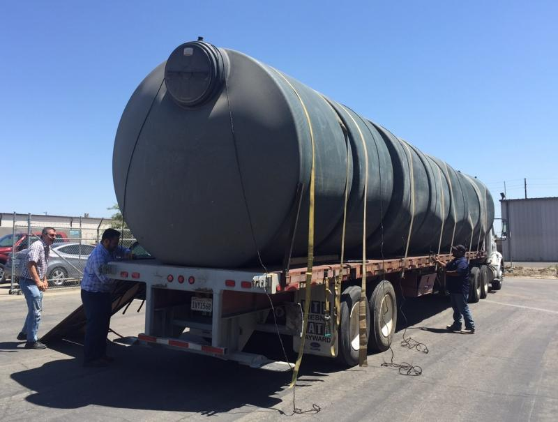 Five 2,500-gallon water tanks wait to be unloaded at the nonprofit Self-Help Enterprises near Visalia, Calif. So far about 140 tanks have been distributed to homes, but at least 1,000 more are needed in Tulare County alone.