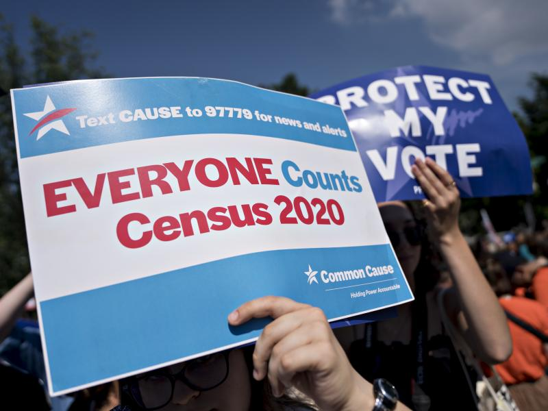 A demonstrator holds a sign about the U.S. census outside the Supreme Court in Washington, D.C., in 2019. The Census Bureau has stopped all work on President Trump's directive to produce a count of unauthorized immigrants that could be subtracted from a k