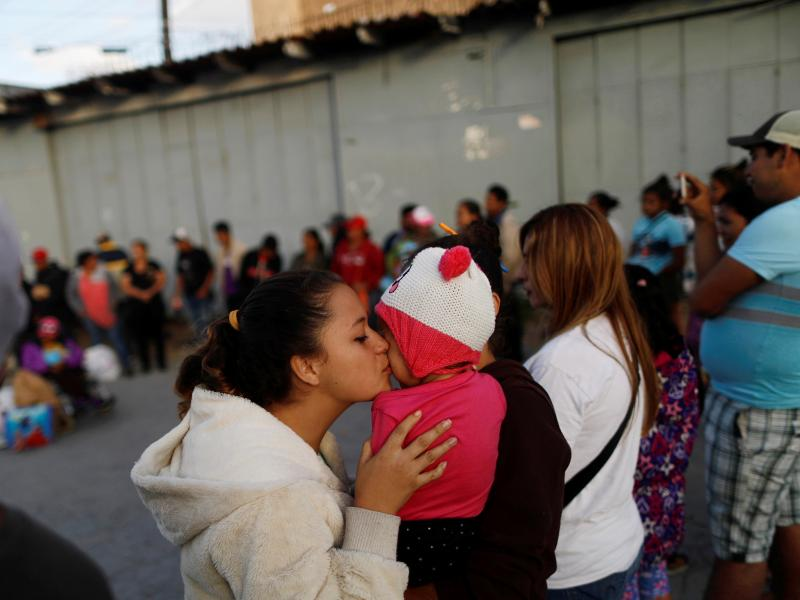 A member of a migrant caravan from Central America kisses a baby as they pray in preparation for an asylum request in the U.S., in Tijuana, Baja California state, Mexico.