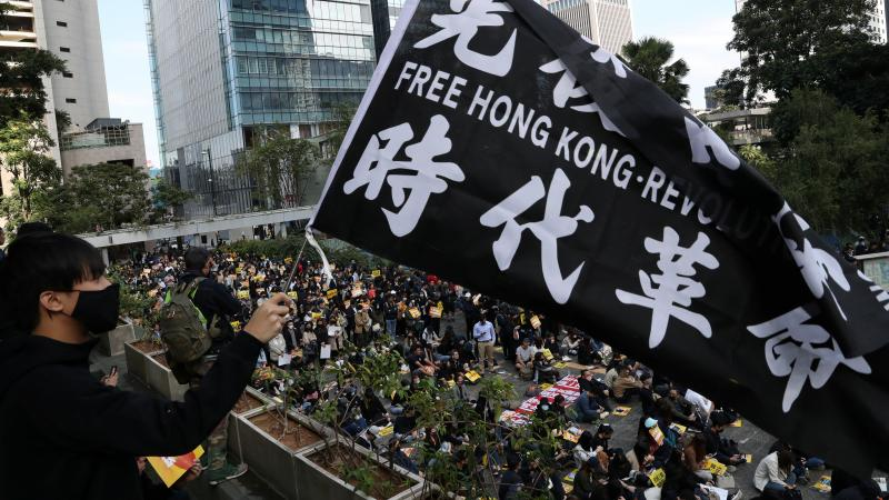 """China urges the U.S. to correct its mistake and stop meddling in Hong Kong affairs,"" a government spokesperson says, as China retaliates for U.S. support of pro-democracy demonstrators. Here, an activist holds a flag at a lunchtime protest Monday at Chat"