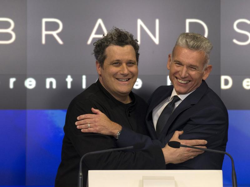 Designer Isaac Mizrahi (left) embraces Robert D'Loren, CEO of Xcel Brands, which once manufactured 70% of its clothes in China. Today that's down to about 20%. The company now manufacturers in a variety of countries, including Indonesia, India and Sri Lan
