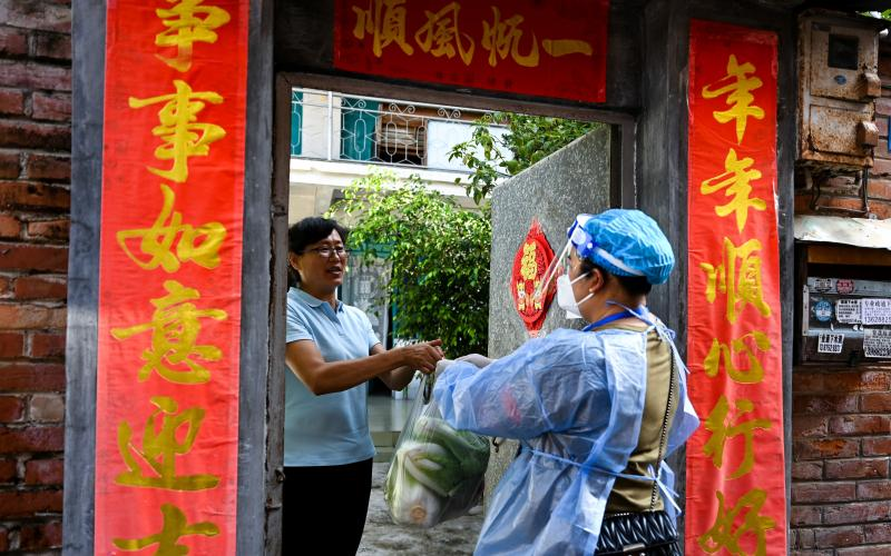 A community worker delivered daily necessities to a household in Ruili City in China's Yunnan Province during a July lockdown triggered by COVID cases. Ruili closed off its city proper and asked all residents to quarantine at home. Classes were suspended.